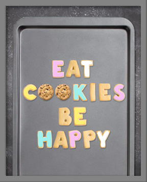 Eat Cookies Be Happy spelled out with cookies cut in the shape of letters on a baking sheet